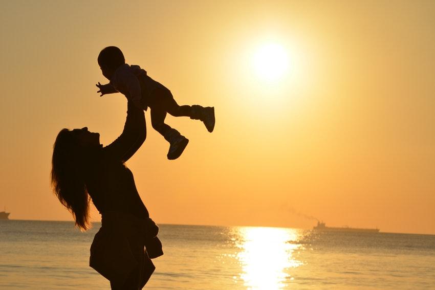 Une mère et un fils devant un coucher de soleil