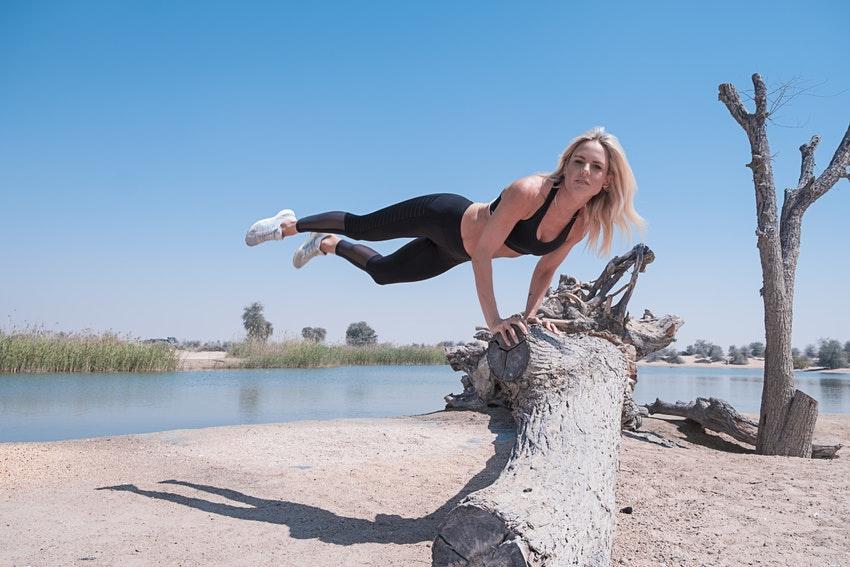 femme sportive sautant un tronc d'arbre